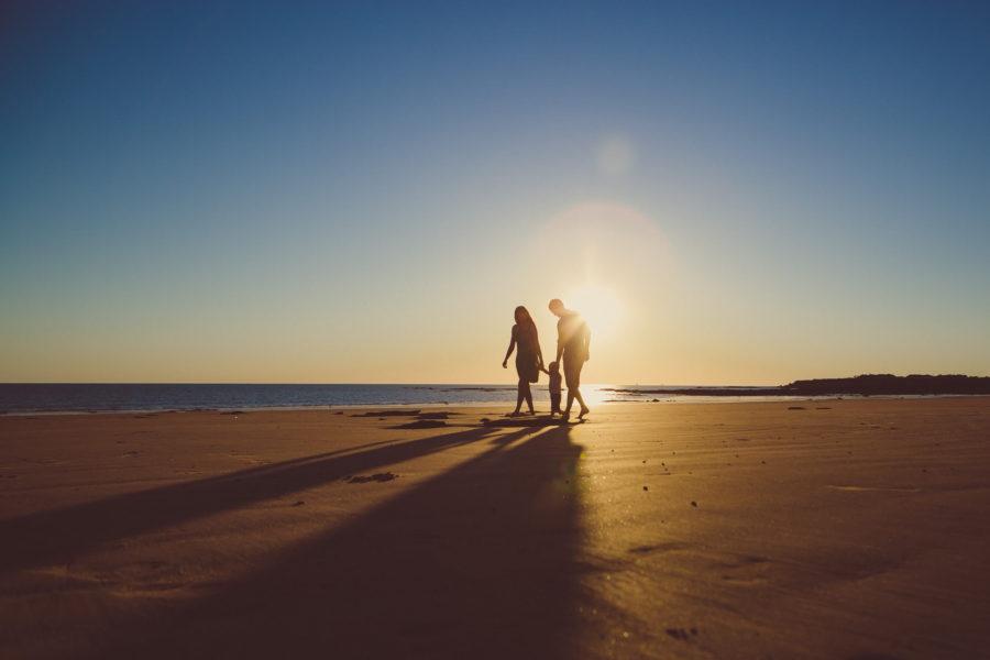 family on beach with long shadows