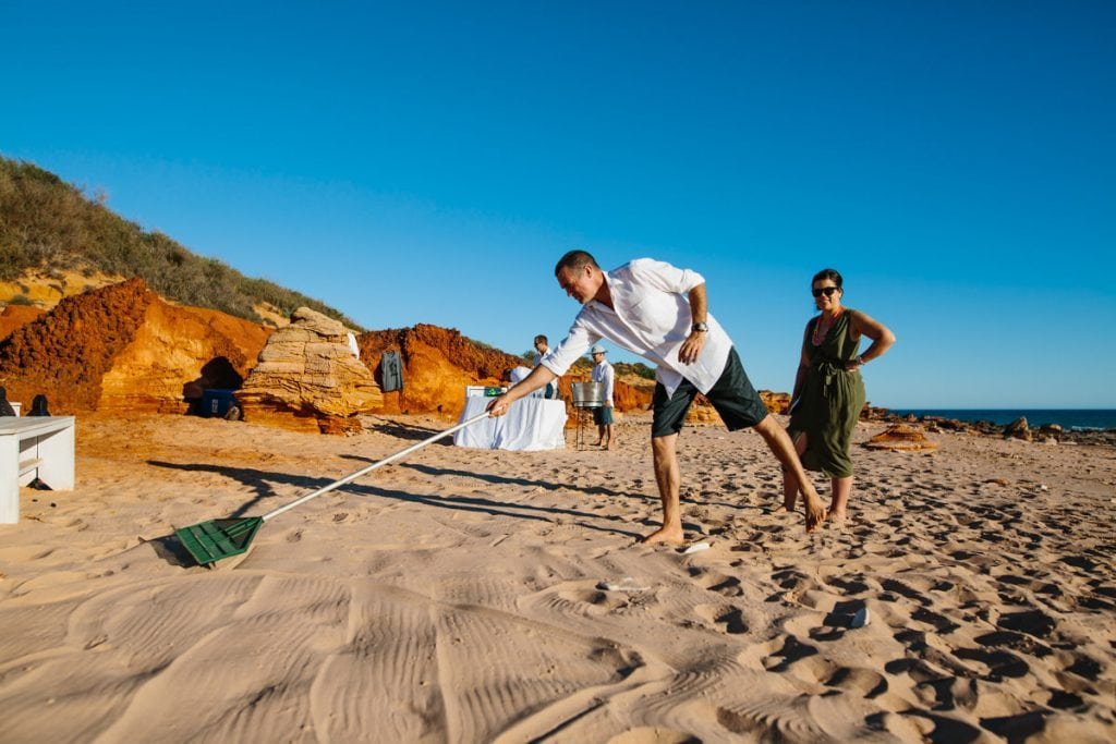 wedding guest raking beach