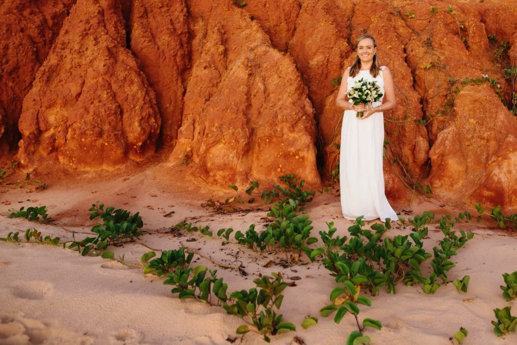 bride with flower bouquet in front of red pindan cliffs