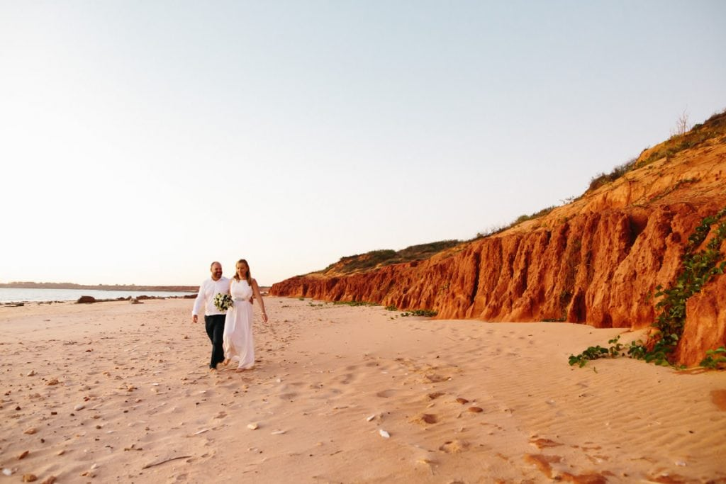 bride and groom walking along beach and red cliffs