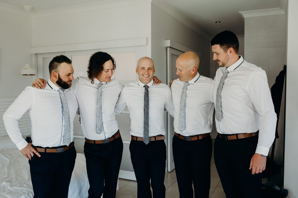 groom with groomsmen standing in half circle in hotel room