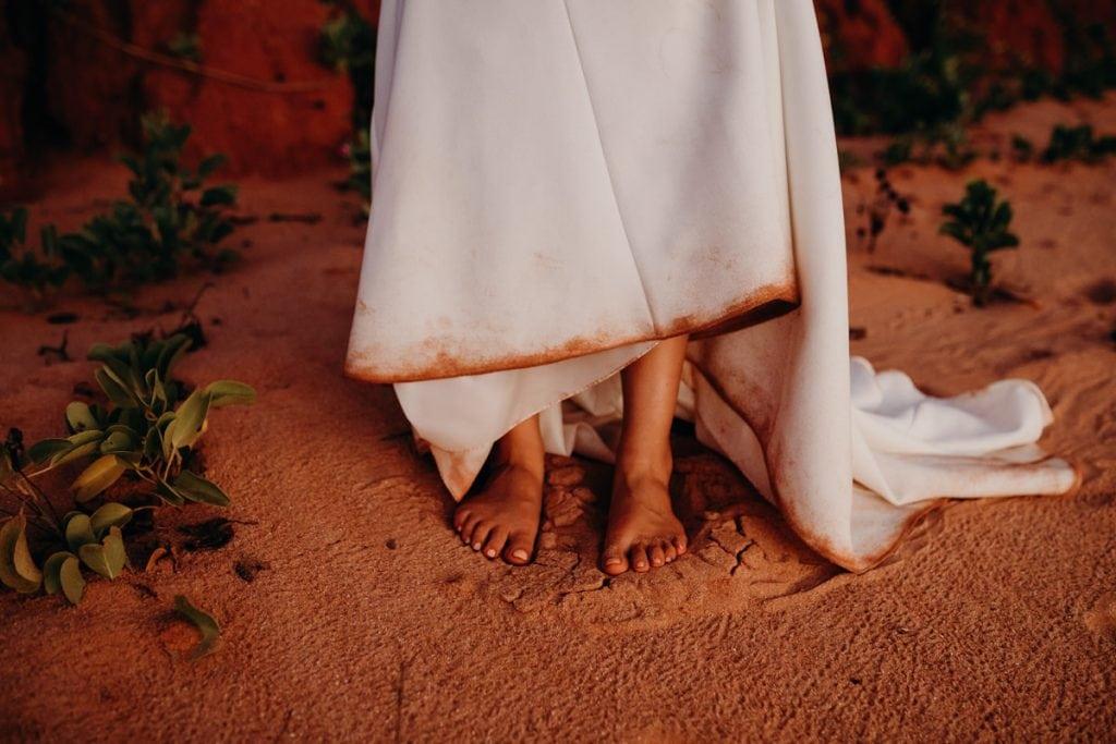 dirty feet of bride on beach with dirty wedding dress