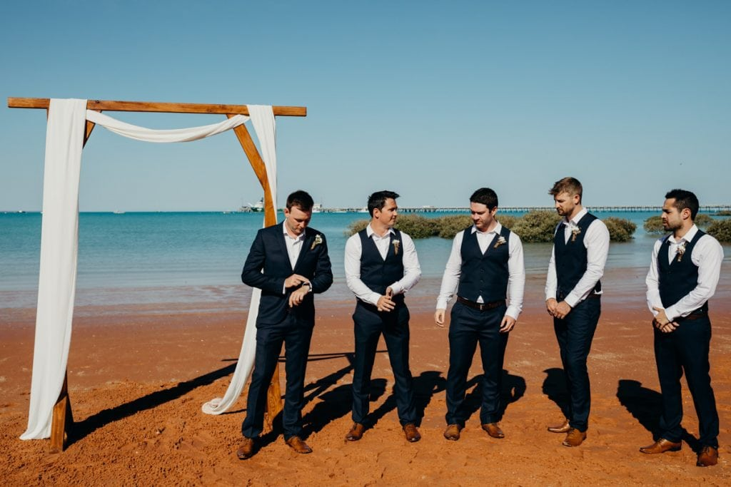 Groom and groomsmen waiting at wooden arbour by Broome Vintage Wedding Hire with Roebuck Bay in the background