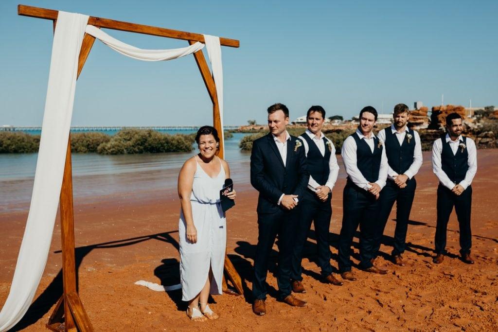 Elle Saunders Broome celebrant with groom under wooden arbour