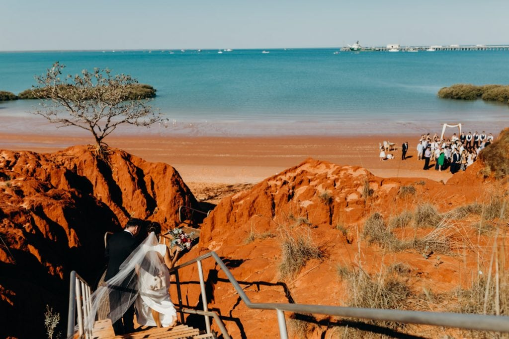 father of the brides walks daughter down to Roebuck Bay at Hovercraft Base in Broome