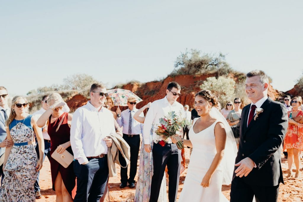 brides smiles while she is walking down the aisle with her father