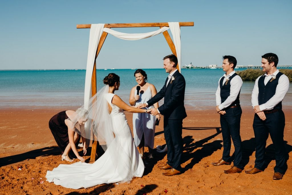 bride and groom holding hands under a wooden arbour with celebrant