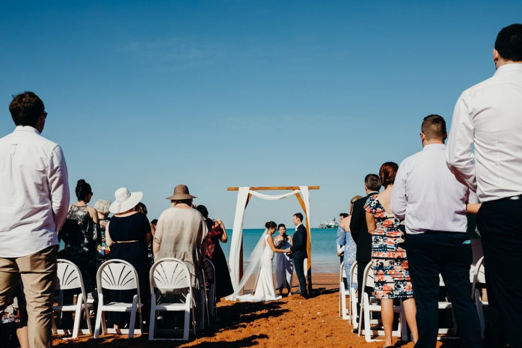 wedding guests are standing during beach ceremony at Broome Hovercraft base