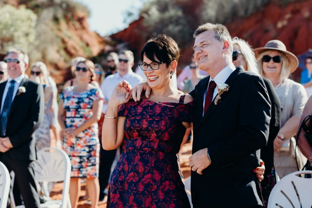 parents of the brides are smiling during the wedding ceremony at Roebuck Bay