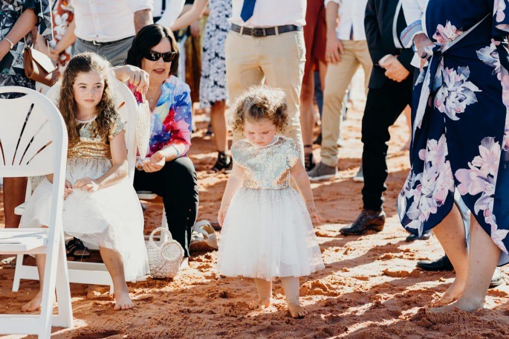little girl in golden dress barefoot at beach wedding