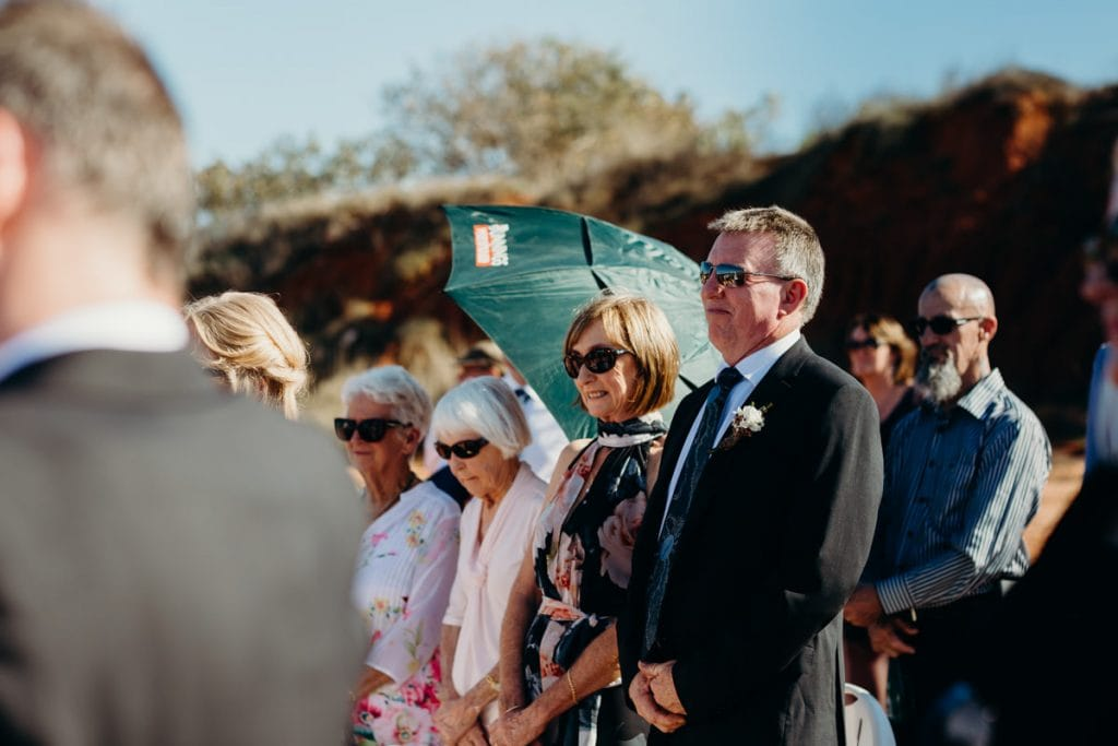 parents of the groom are looking on at son's beach ceremony