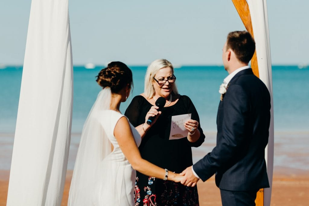 bride and groom holding hands during their wedding ceremony with friend giving a speech