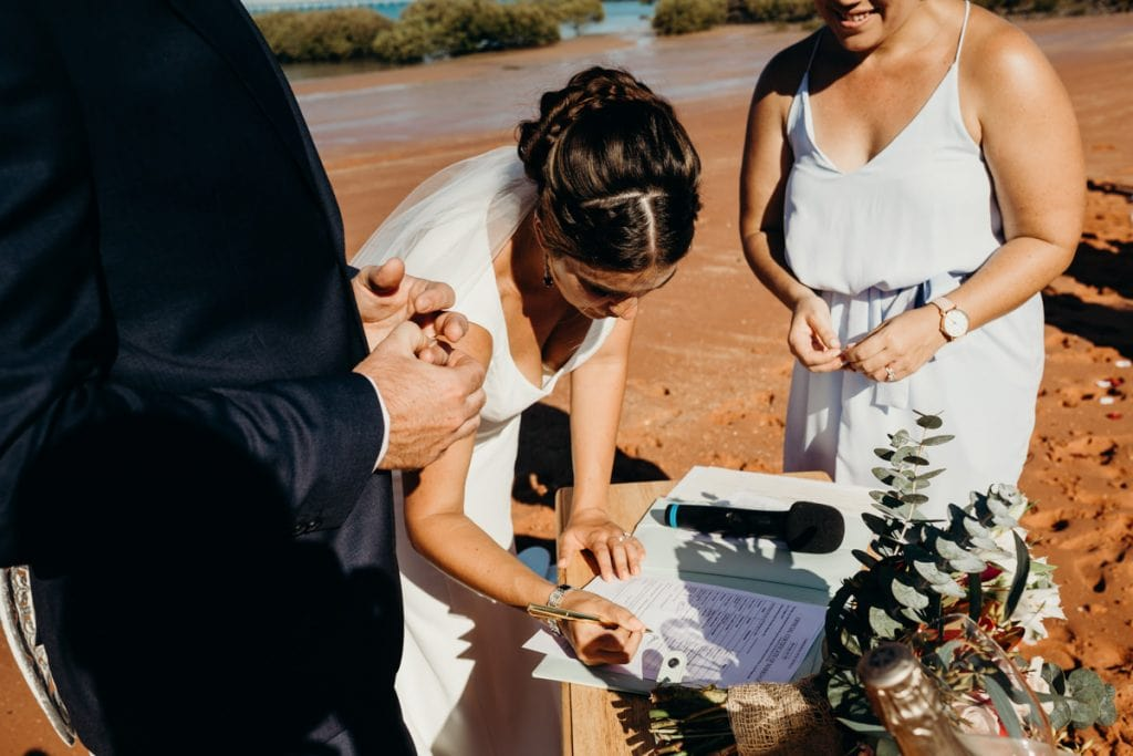 bride is signing wedding document on the beach