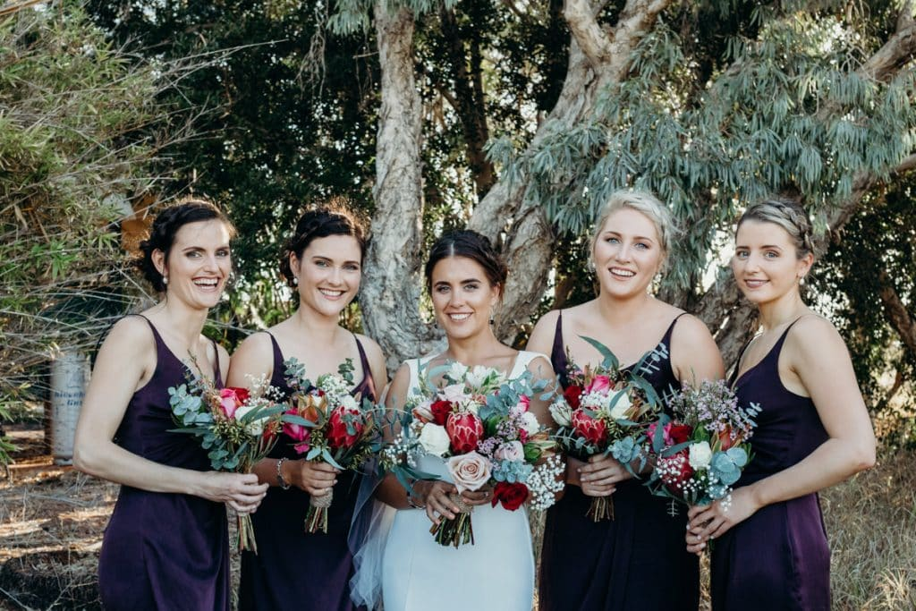 bride with her bridesmaids and beautiful flower bouquets