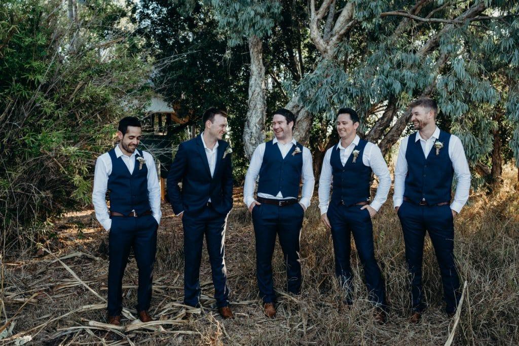 groom and groomsmen standing under a tree