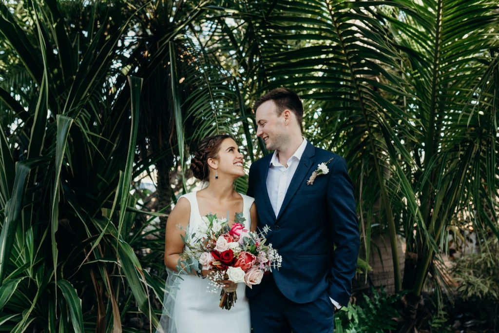 bride and groom portrait with palms in the background