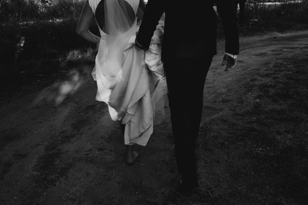 black and white shot of wedding couple walking with groom holding dress up