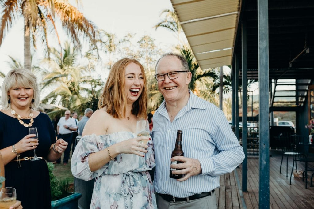man and woman laughing with drinks in their hands