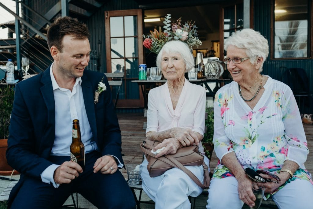 man and two old ladies sitting on bench