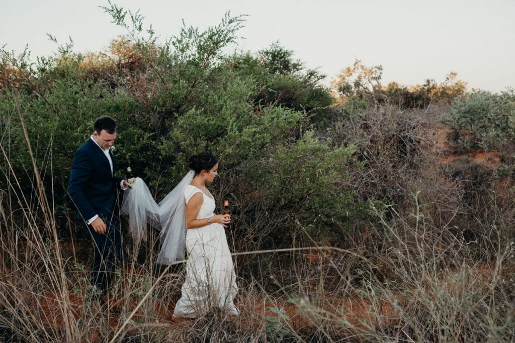 bride and groom walking through high grass with drinks in their hands