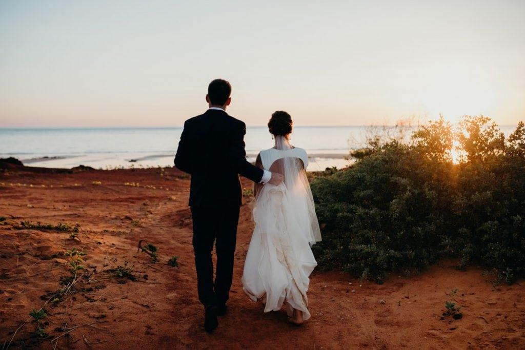 wedding couple walking towards the beach with the sun setting