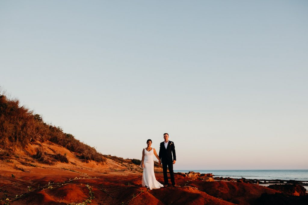 couple of people in wedding attire standing on red cliff