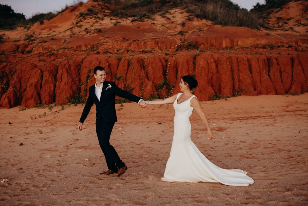 Man in suit dragging bride along on beach