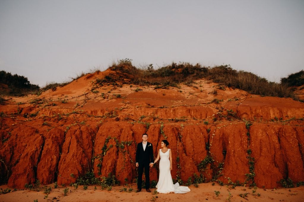 wedding couple stands in front of red cliff with bride looking at groom