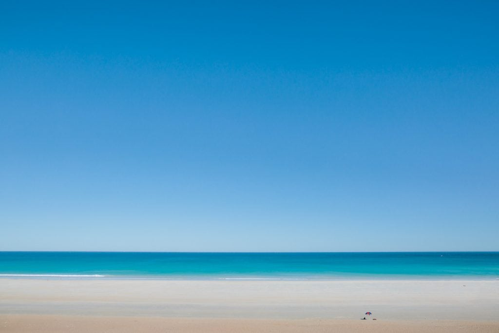 Cable Beach in Broome with one sun umbrella in the far distance