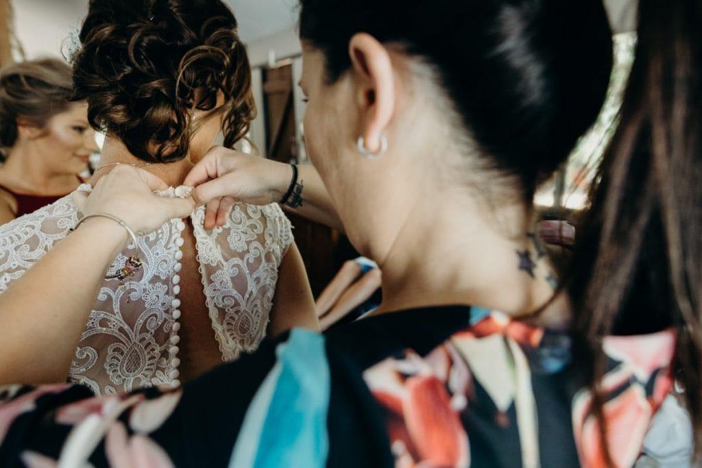 girlfriends helping bride into wedding dress