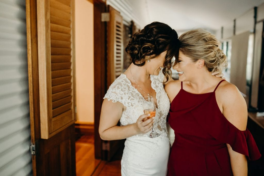 bride and her girlfriend are hugging and smiling