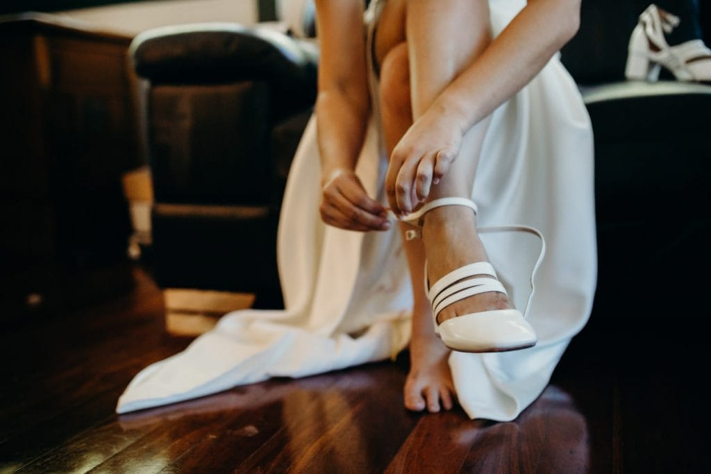 bride is putting on her white wedding shoes