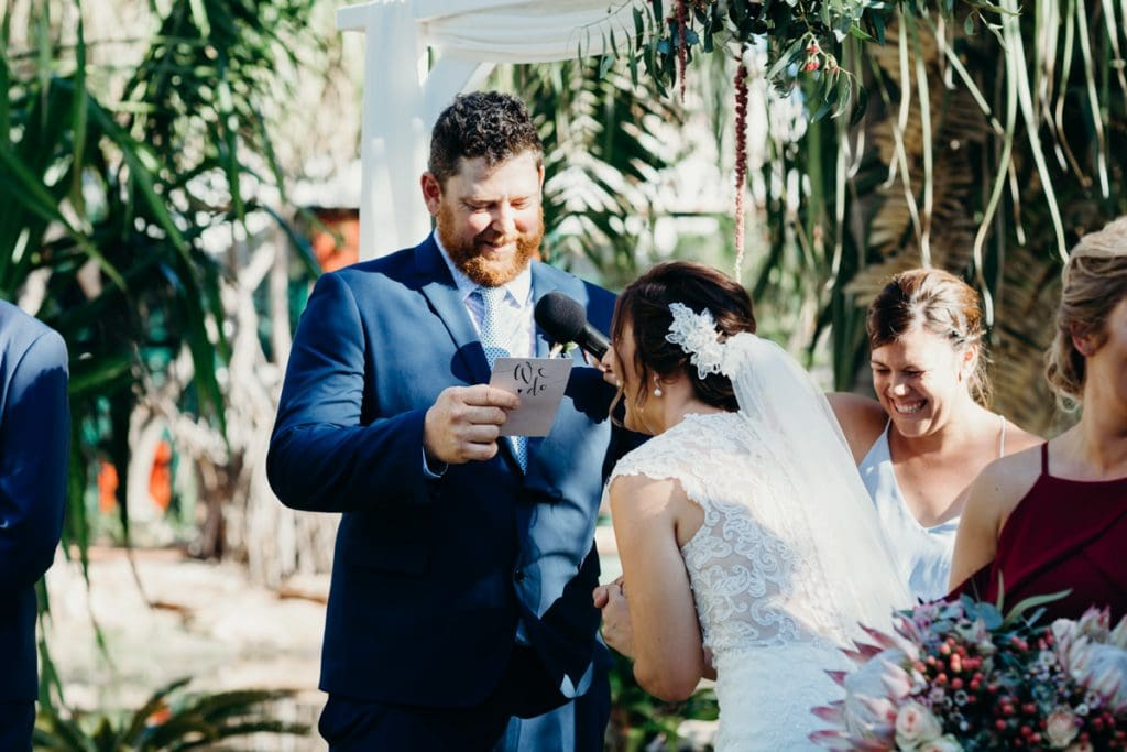 groom read his vows to bride who is laughing