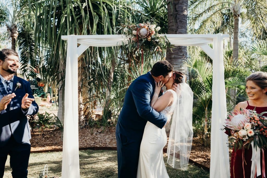 freshly married couple has first kiss under white arbour