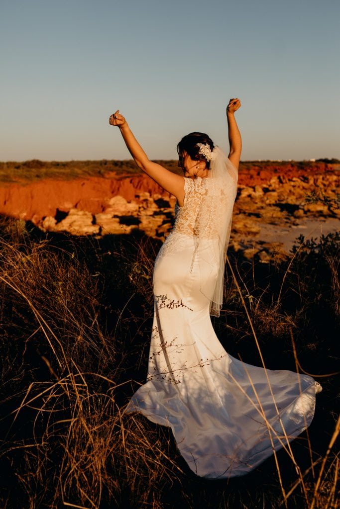 bride at sunset with arms in the air