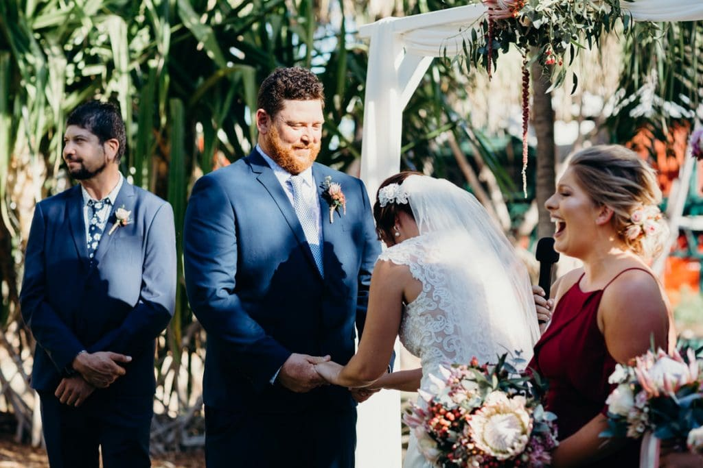 bride and groom smiling under white arbour