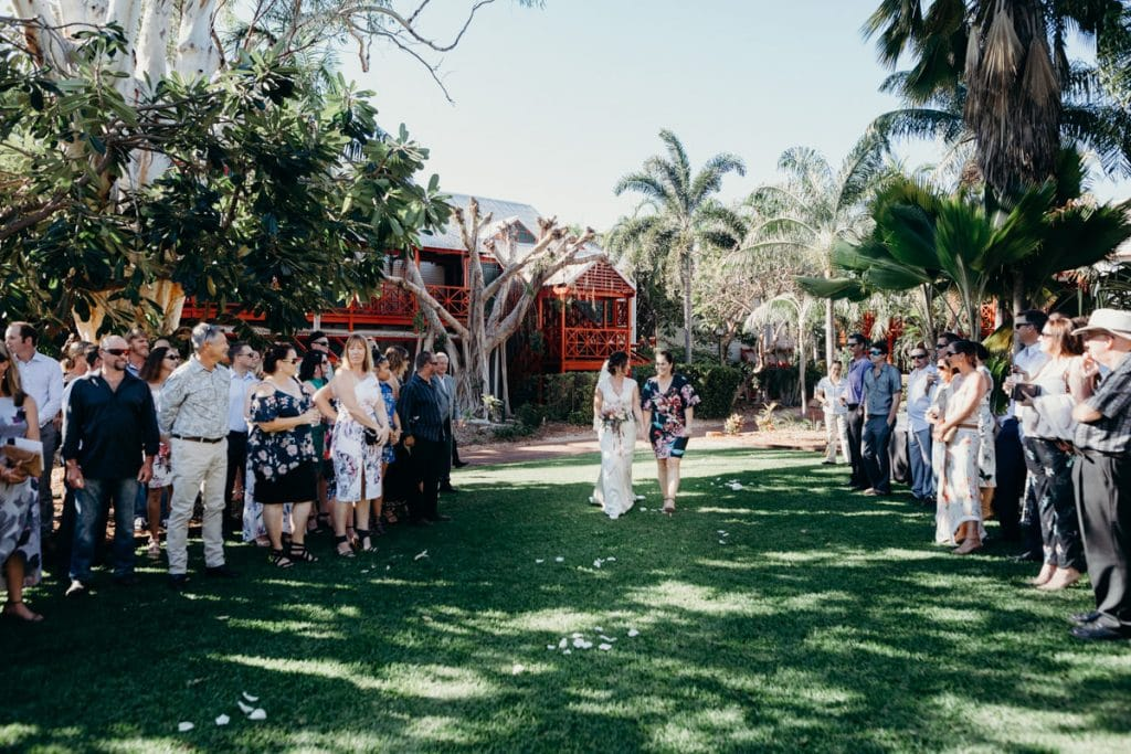 bride walks down the aisle at Lily Pond Lawn at Cable Beach Club Resort