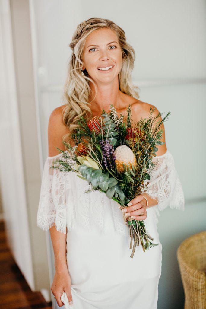 Portrait of bride in her wedding dress with wildflower bouquet in Broome hotel room
