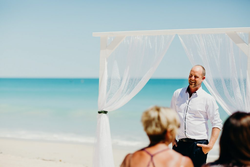 groom standing under a white arbour on Cable Beach waiting for his bride