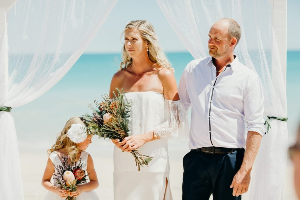 Bride and groom standing under white arbour on Cable Beach