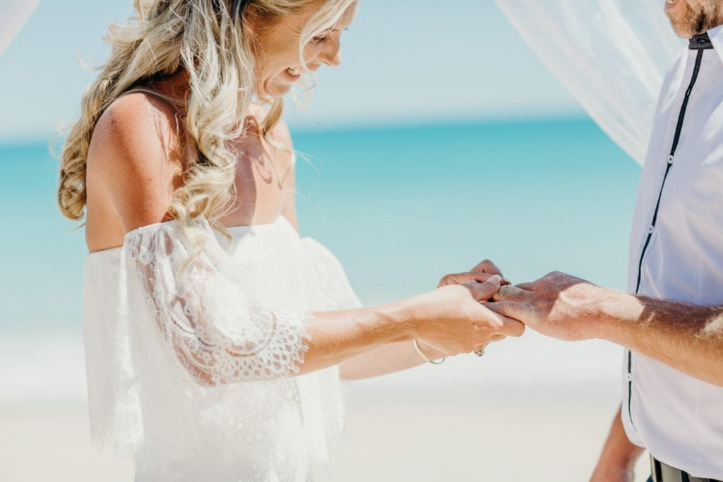 bride and groom exchange rings on Cable Beach