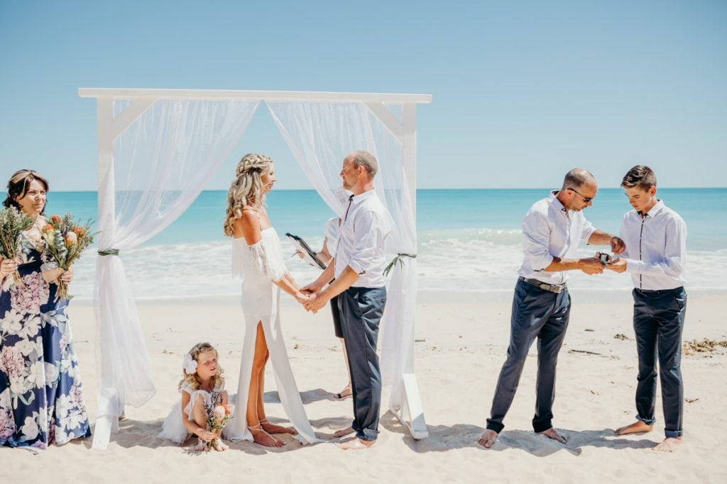 Best man getting rings during beach wedding ceremony
