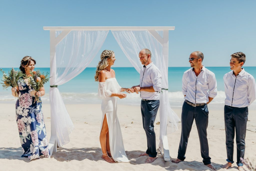 wedding couple on Cable Beach under white wooden arbour