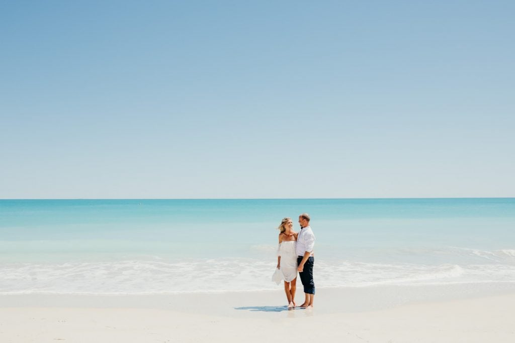 wedding couple standing on the waters edge with blue ocean behind them