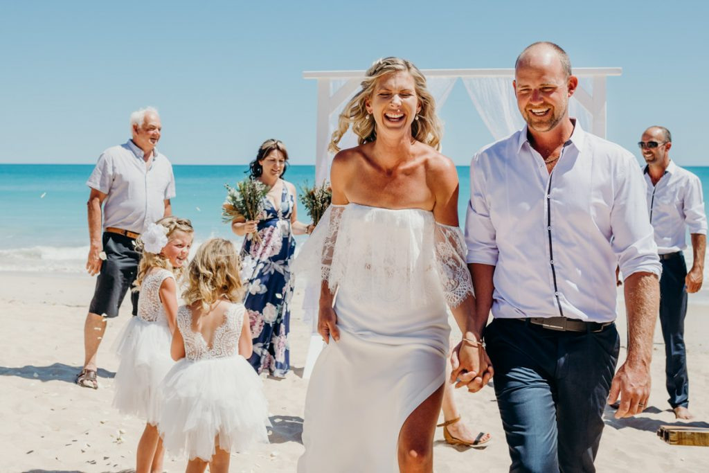 freshly hitched couple walking on Cable Beach