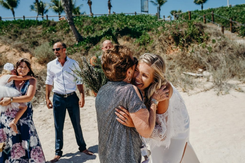 grandmother congratulates bride after beach ceremony