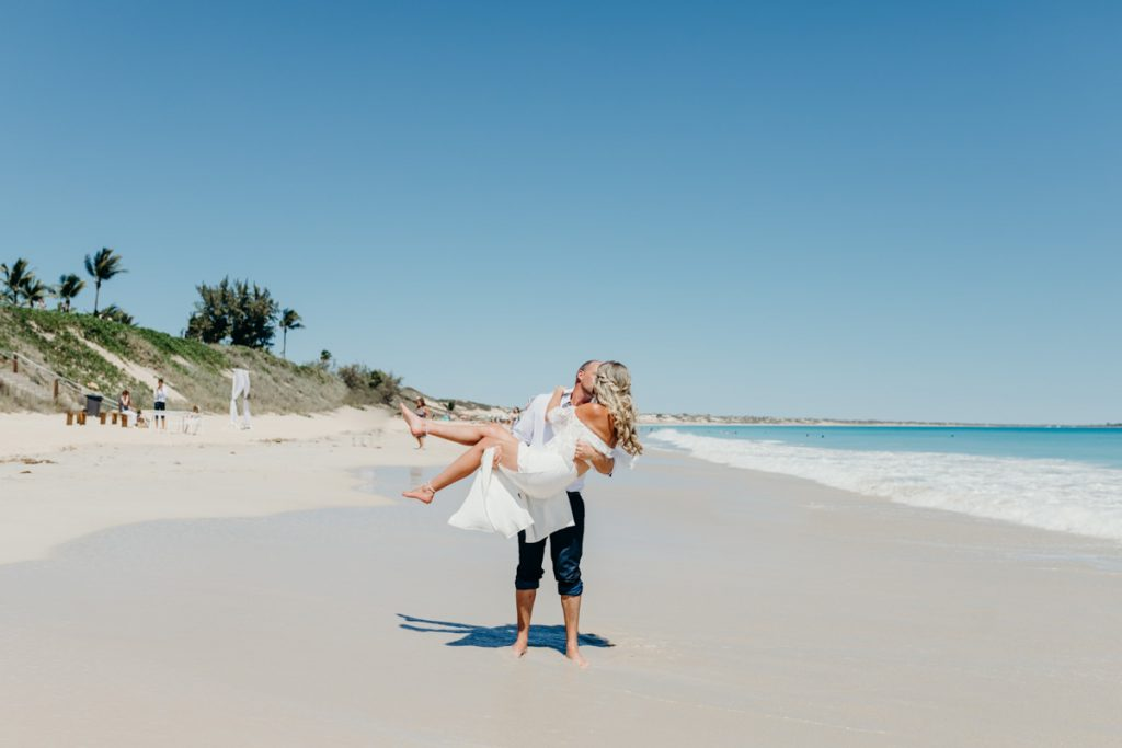 groom holding his bride in his arms on white sandy Cable Beach