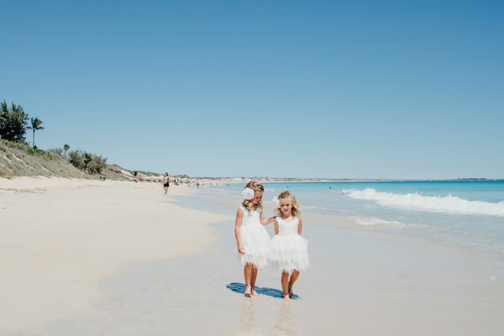 flower girls in white dresses walking along Cable Beach in Broome