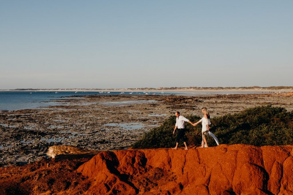 bride and groom walking along red pindan cliff with view over Cable Beach