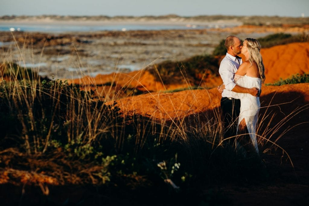 Kissing wedding couple at Gantheaume Point with long grass in the foreground